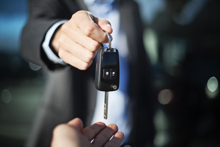male adult dealer hand giving car keys to female person