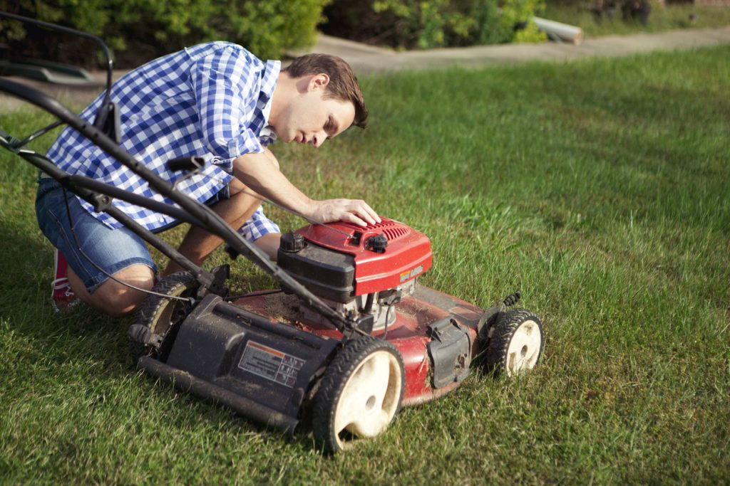 Man provides maintenance for his lawn mower.