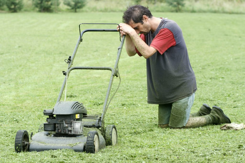 A man on his knees with his lawn mower, tired from mowing his lawn