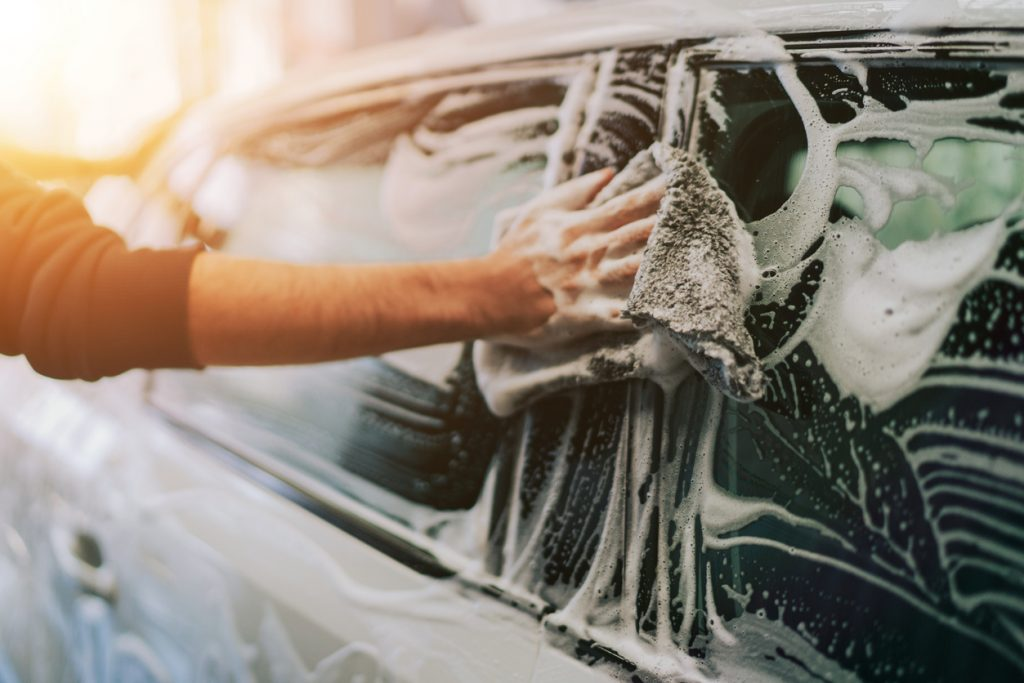 Man cleaning his car with soap and a rag
