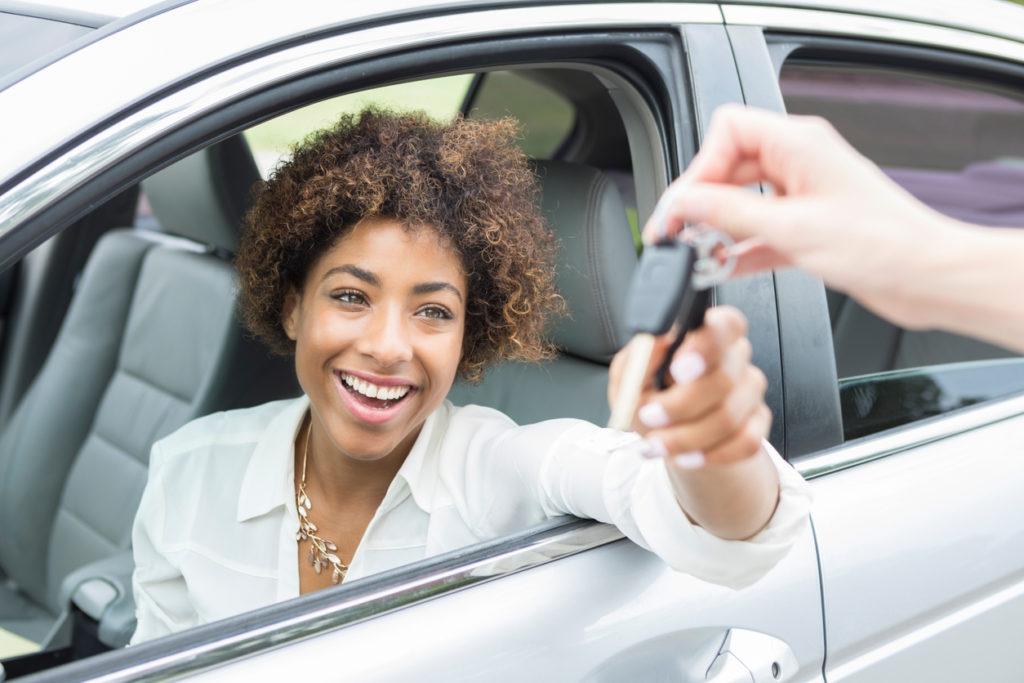 Excited young woman accepts new car keys