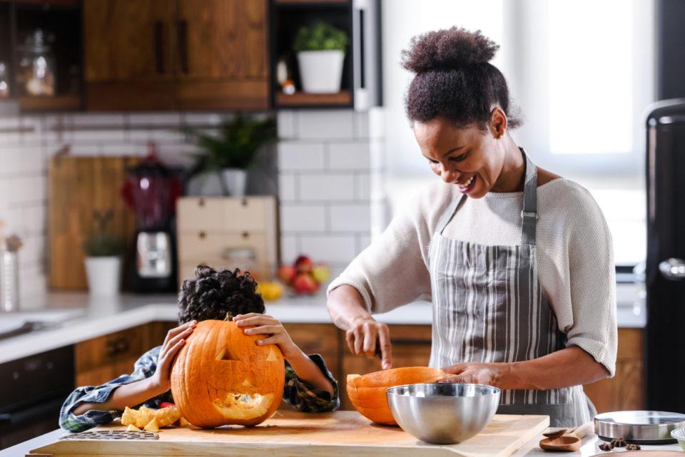 Mother and son carving pumpkin making Jack-o-Lantern