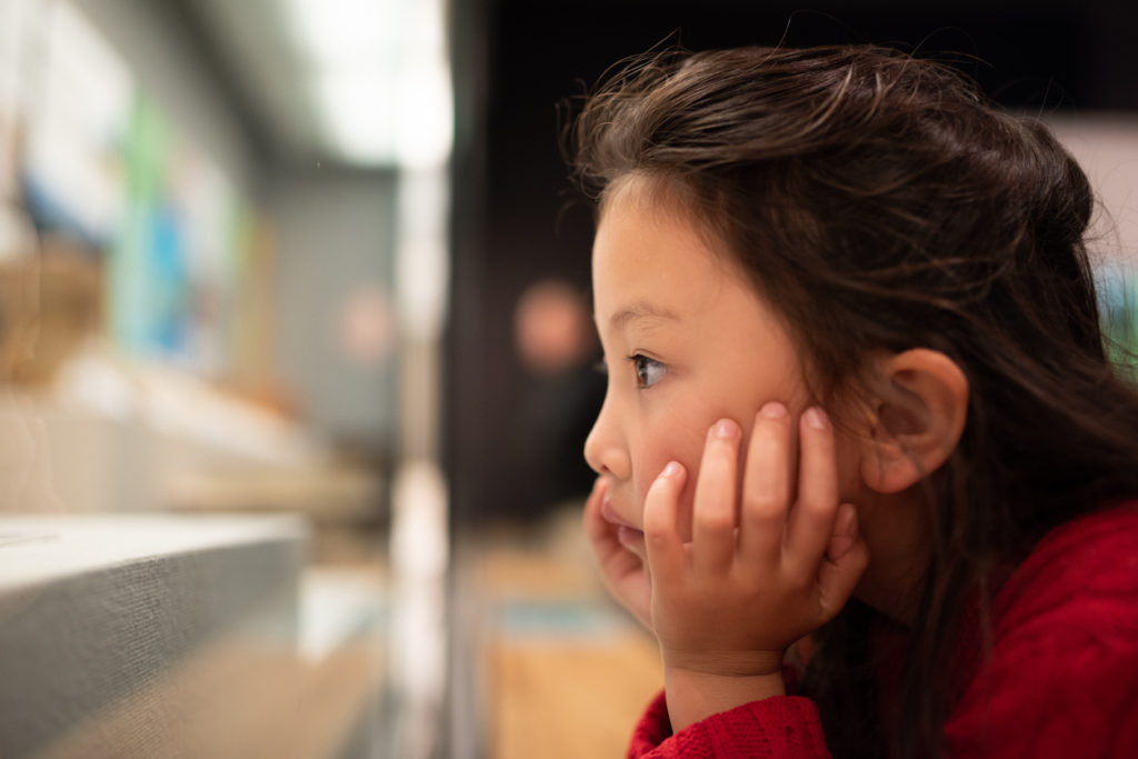 Little girl looking at science museum exhibit