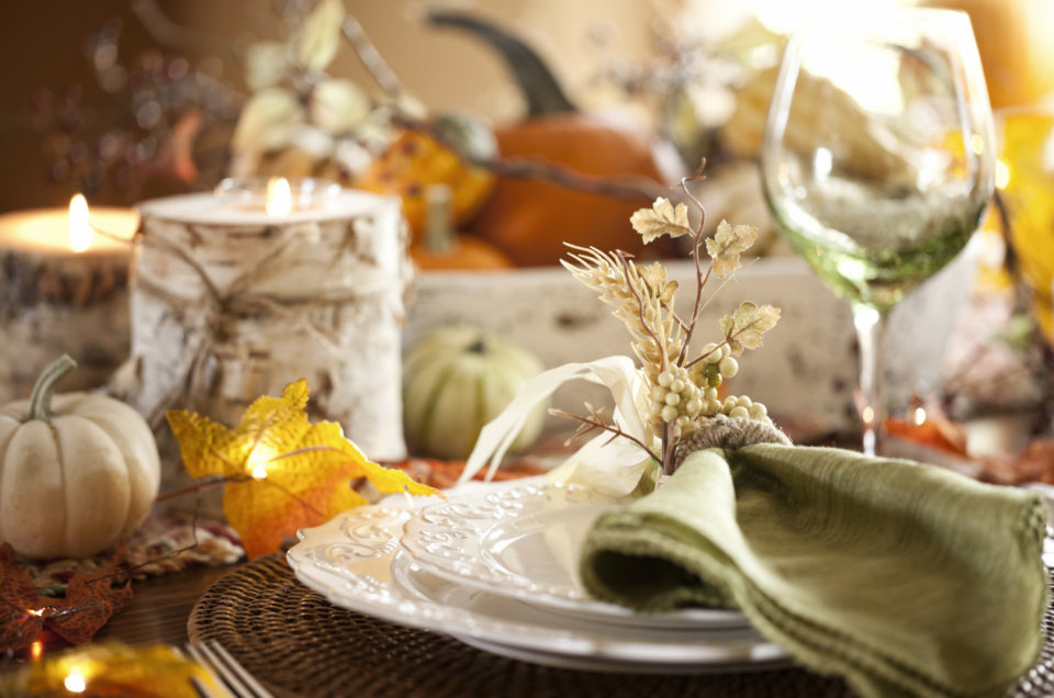 Autumn holiday Thanksgiving dining with beautiful traditional centerpiece filled with pumpkins and gourds.