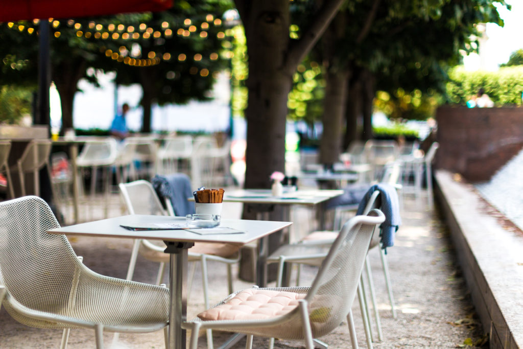 Color image depicting chairs and tables arranged at an outdoors cafe in central London, UK. It is a beautiful green space lined with trees and illuminated with fairy lights. There are bowls of sugar on the tables, but there are no people around.