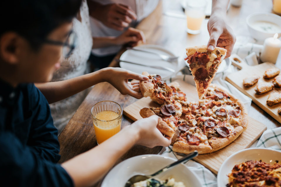 Group of friends eating pizza at a restaurant