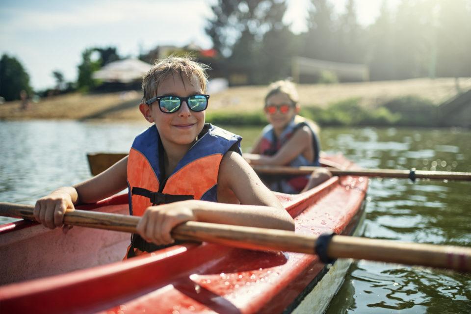 Two boys enjoying kayaking on lake
