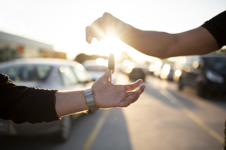 Owner passing keys to salesperson for trade in