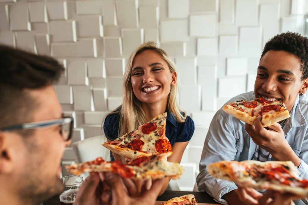 Happy friends eating pizza together