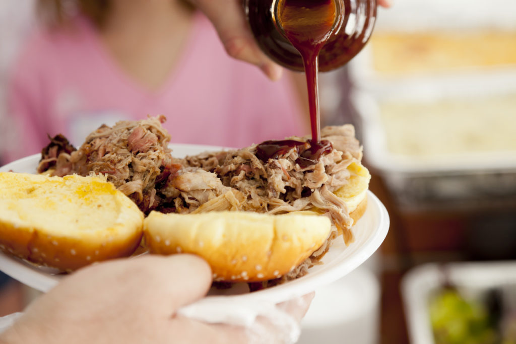 Adding barbeque sauce to a pulled pork sandwich.